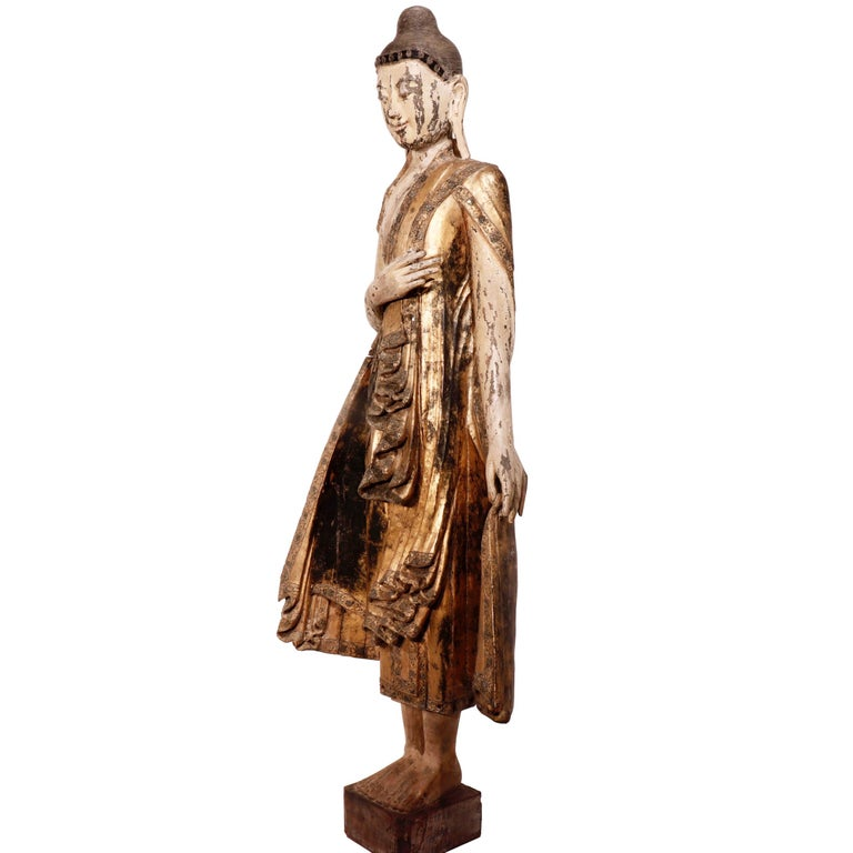 Burmese Mandalay carved wood figure of the standing Buddha on a square base, the left hand is in the varada or boon-granting mudra, the right held up towards the chest, costumed in edge-decorated robe with glass insets, resembling a cape with the