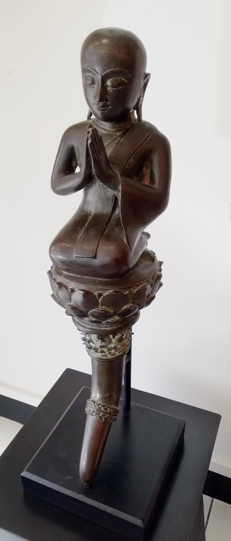 Burmese monk in bronze 18th century, monk seated on a horn decorated with lotus flowers on top, with hands in prayer.