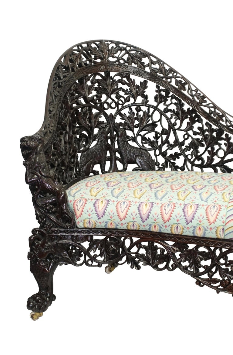 Elaborately carved Padouk wood settee or sofa. Carved with oak leaves, acorns, hunting dogs with inset upholstered cushion. Great detailing on the curved arms with snarling dogs among clusters of grapes, standing on cabriole legs with hairy paw