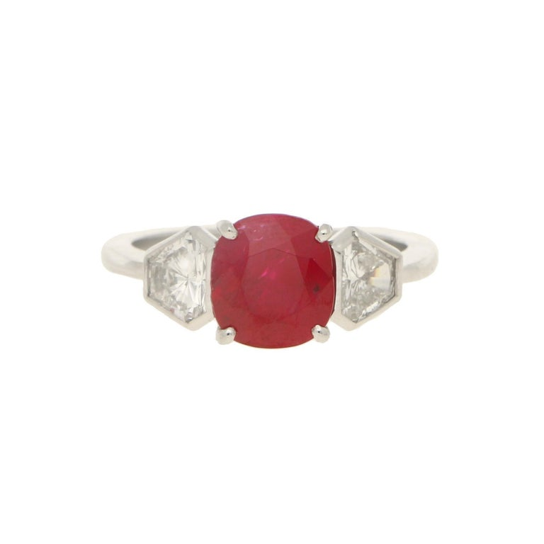 A gorgeous Burmese ruby and diamond three stone engagement ring set in platinum. The piece is centrally set with an incredible cushion cut 3.11ct Burmese ruby that has an amazing luscious colour. It is then sided with two trapezoid cut diamonds,