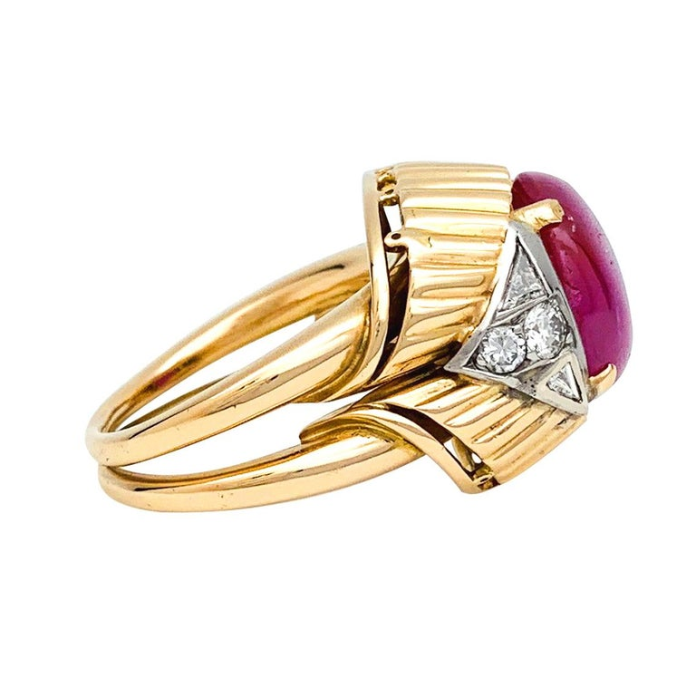 A 18Kt yellow gold and platinum ring, centered with an about 6,40 carats ruby cabochon, framed by four triangular diamonds and four brilliant cut diamonds.  French gemological Laboratory certificate stating that the stone is from Birmanie, unheated