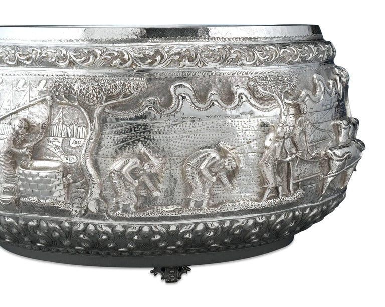 This unusually large Burmese silver bowl is most certainly the work of a master artist. A tour-de-force of silver hailing from Burma, or Myanmar, this bowl exhibits some of the most magnificent high-relief repoussé decoration. A continuous tableau