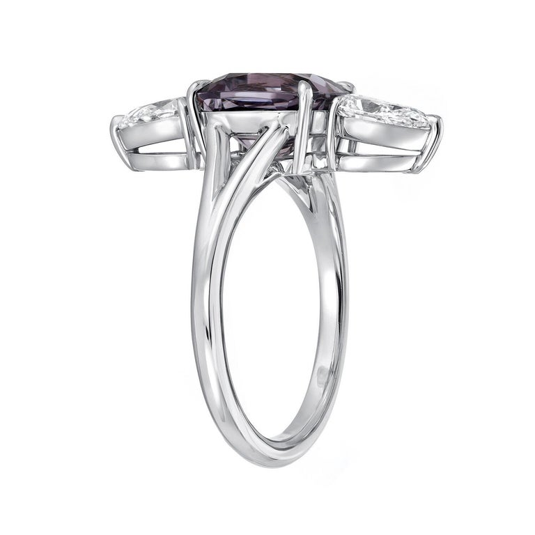 Spectacular 3.14 carat cushion cut Burma Spinel, displaying a violet hue with grayish undertones, and a pair of GIA certified F/VS1 pear shape diamonds weighing a total of 1.00 carat, are set vertically in this exquisite hand crafted platinum