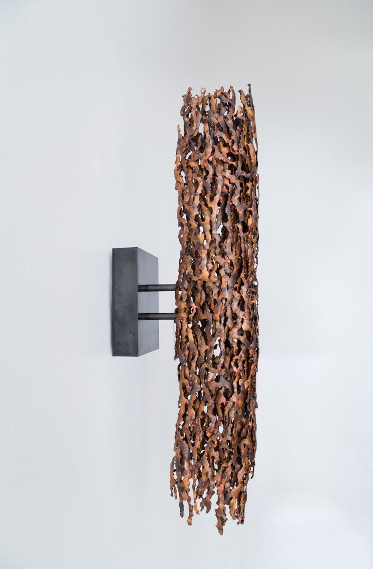The burnt copper form light makes a bold statement. The body of the light is hand assembled from heat-formed copper pieces into an intense compact shape. The meandering edges and varying thickness of the individual pieces contribute to a unique and