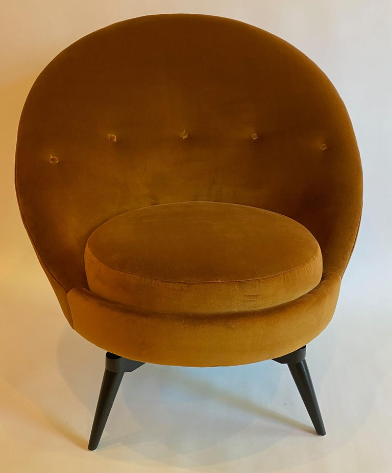 Swivel egg chair in the French midcentury style. This sophisticated chair is upholstered in heavy-weight burnt orange/gold velvet. This super stylish and versatile example is as comfortable as it looks and is painstakingly patterned with a hardwood