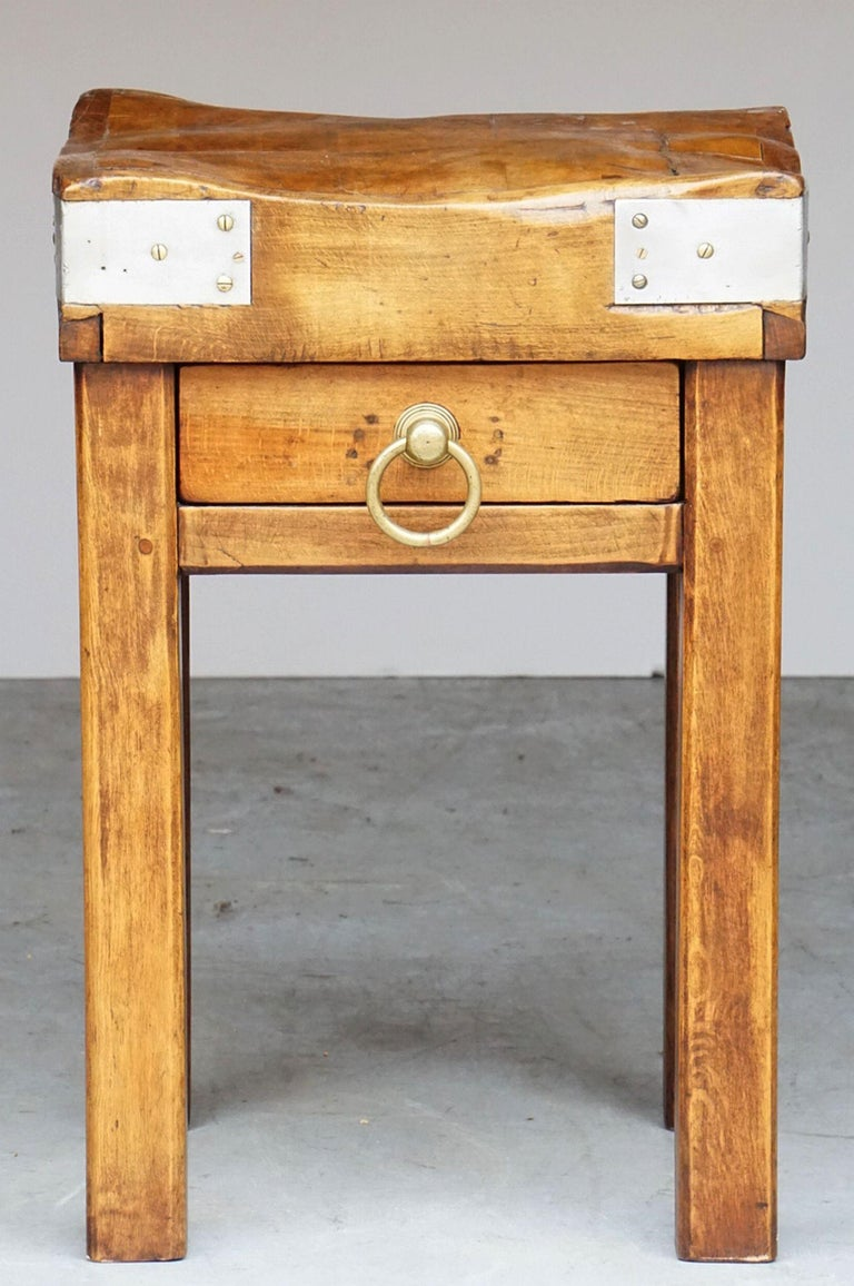 A fine French butcher's chopping block or table, featuring a large, square sloping block or slab of bound wood set upon a four-legged support stand of stained pine. Stand with drawer and large brass ring pull.