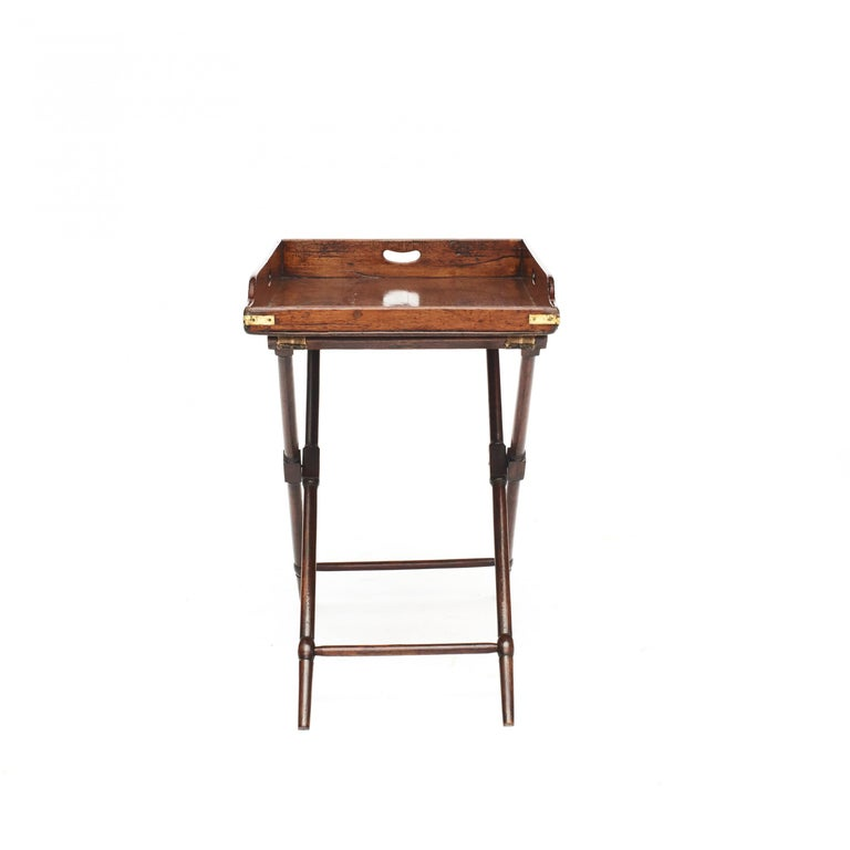 A 19th century English mahogany butler's tray table. With removable handled tray top with brass fittings on a collapsible X-frame stand. Very good patina. Victorian, England, 1850-1860.