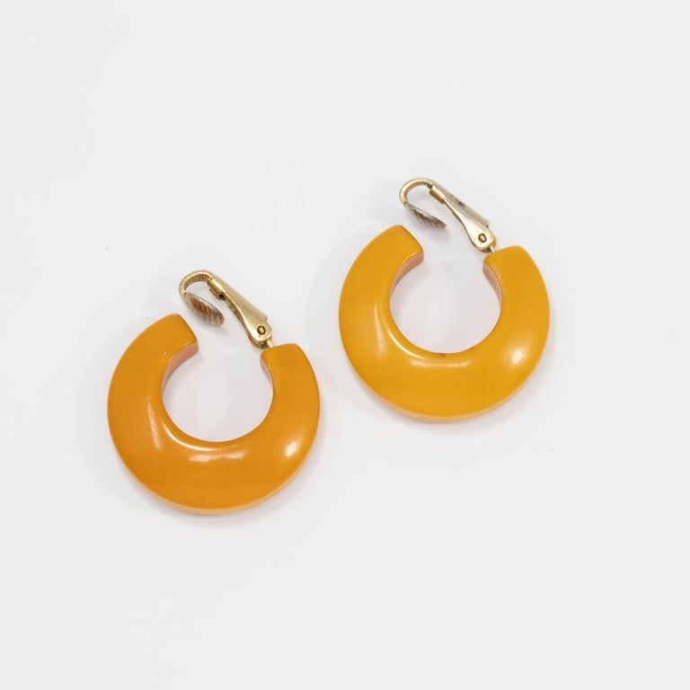 A pair of bright butterscotch yellow huggie earrings. Vintage bakelite with goldtone clip on findings.  Circa early to mid 1900s.