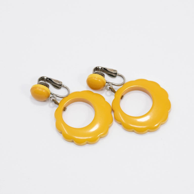 Spectacular pair of bakelite earrings! Bright butterscotch yellow bakelite accents hang off of studded silver-tone clip ons.