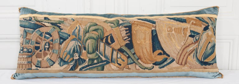 17th century tapestry fragment depicting a soldier's gear in shades of blues, creams, greens and gold, bordered with antique gold metallic galon on Wedgwood blue velvet. Hand trimmed with vintage gold metallic cording, knotted in the corners. Down