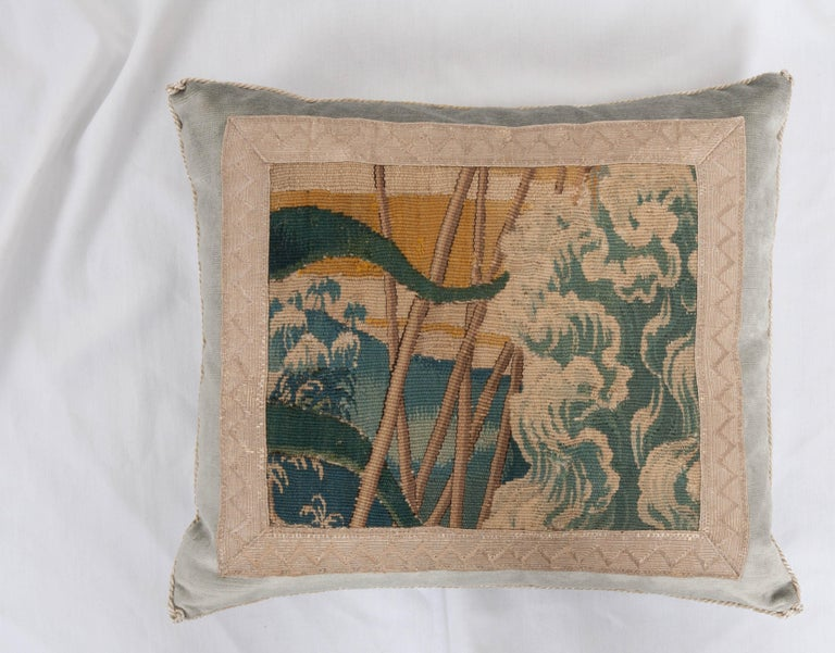 Antique tapestry fragment in shades of blue, green, gold, and khaki framed with antique silver metallic galon on pale French blue velvet. Hand-trimmed with vintage silver-metallic cording which is knotted in the corners. Down-filled. Designed by