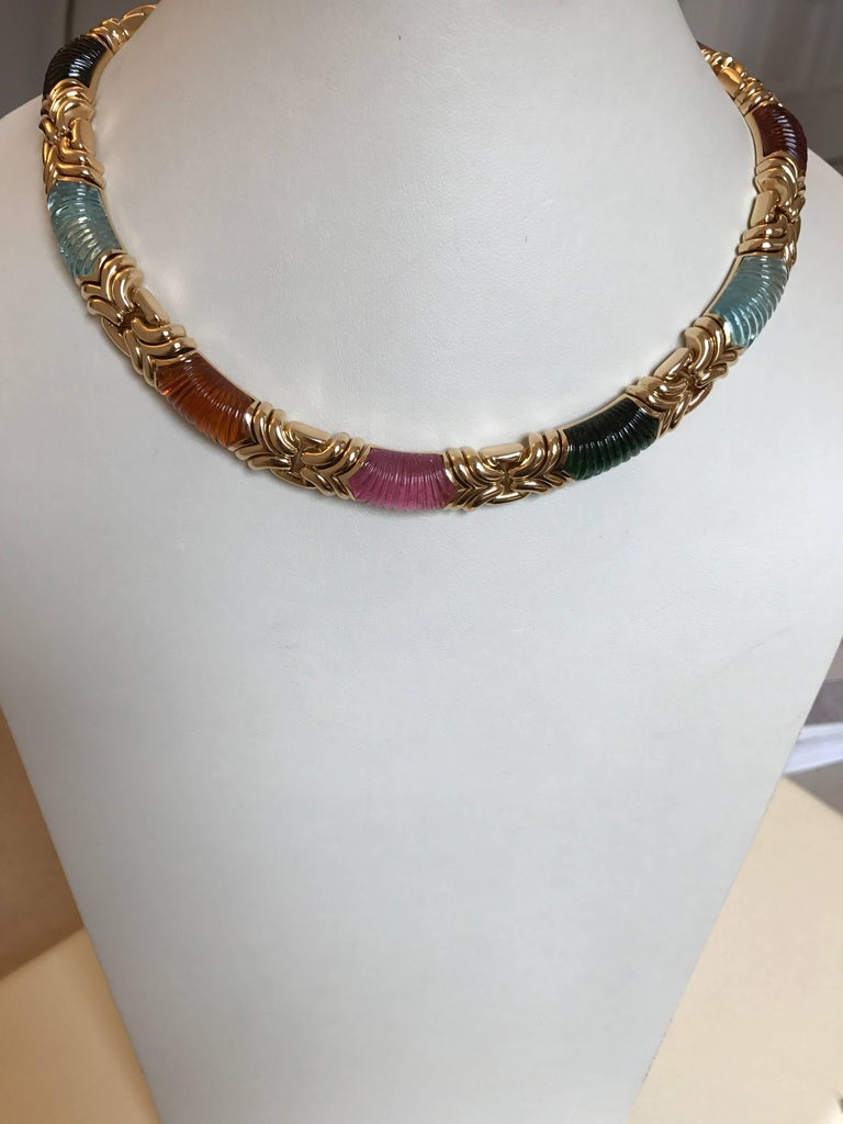 A stunning and iconic 18ct yellow gold necklace incorporating three pink tourmaline, three green tourmaline, three citrine and two aquamarine carved gemstone sections, signed and numbered by BVLGARI, circa 1985 - 1900.  The necklace is in superb