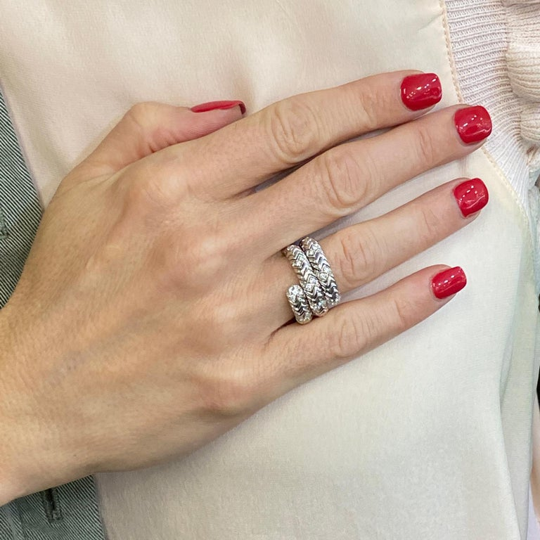 This popular diamond ring by Bvlgari is part of the Spiga Collection. The flexible ring will fit ring sizes 6.5-7.5, and measures 14mm in width. The ring features approximately .60 carat total weight of diamonds set in 18 karat white gold. Weight: