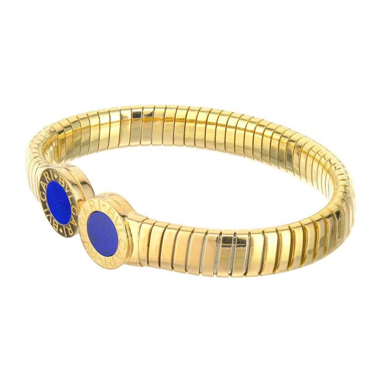 Bvlgari 18k Yellow Gold Tubogas Lapis Bangle Bracelet. Fits a 7 to 7.75 inch wrist.  2 Round Lapis Lazuli 18k Yellow Gold 39.4 Grams Stamped: 750 Hallmark: Bvlgari Width: 13mm Thickness: 4.24