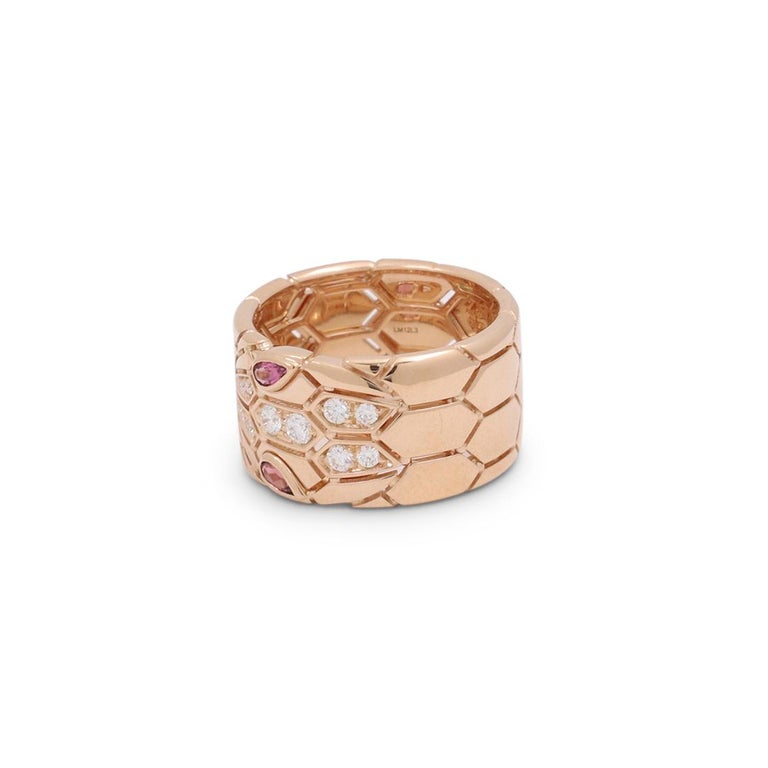 Authentic Bvlgari 'Serpenti Seduttori' ring crafted in 18 karat rose gold. A new take on the brand's iconic snake design, the wide band features a distinctive snakeskin pattern and snake head set with rubellite eyes. The ring is finished with 12