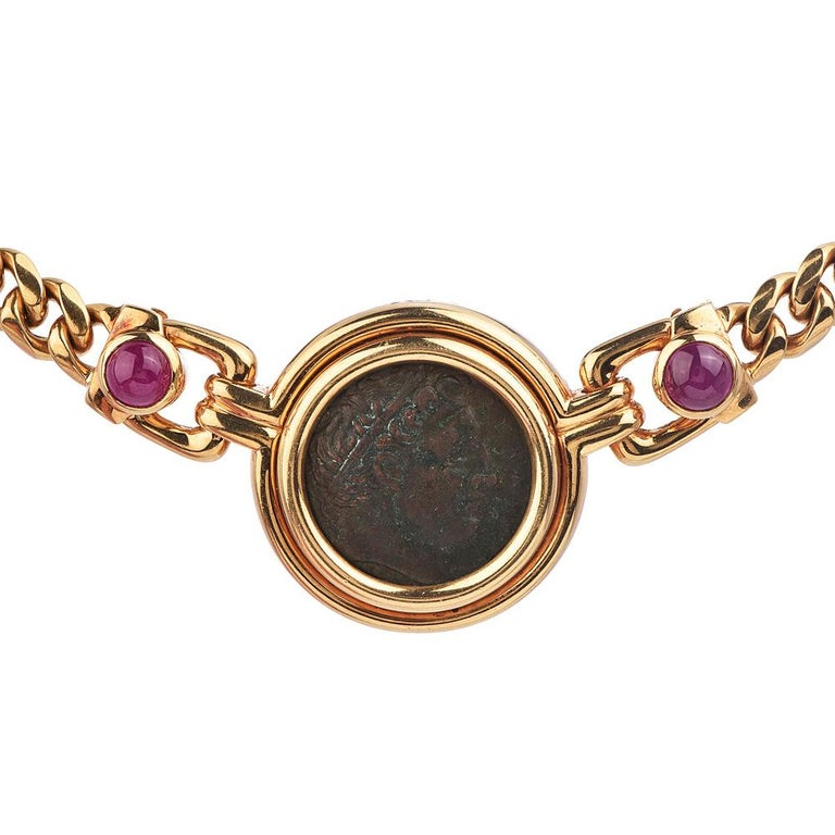 This vintage Bvlgari piece is designed as a curb link chain in 18k yellow gold with gold-framed of the ancient bronze coin as a pendant.  Bezel set with two round cabochon genuine rubies weighing approx. 3.00 carats in total and one round diamond