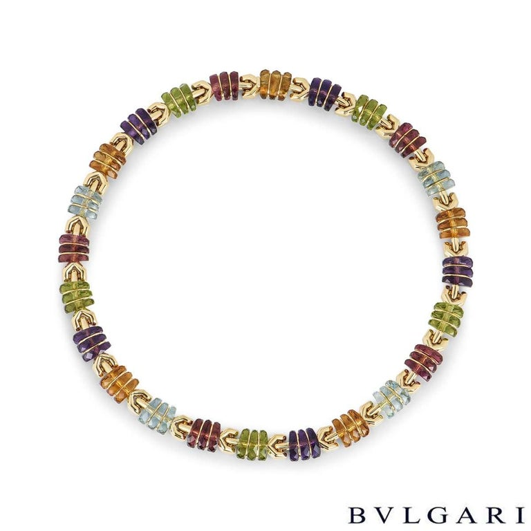 An eye-catching 18k yellow gold multi-gem set collar necklace by Bvlgari. The necklace is made up of 24 alternating gem-set links, featuring amethyst, citrine, aquamarine, tourmaline and peridot. The necklace measures 1cm in width and is 15.7 inches