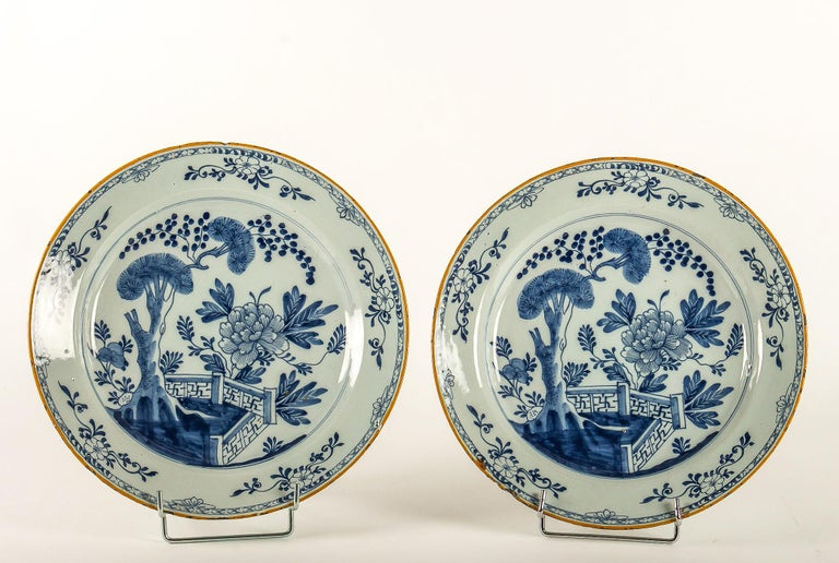 Sign by Ax Porcelain Factory, mid-18th century, Magnificent pair of Faience delft round dishes  Magnificent and rare delft pair of faience dishes, hand painted in a blue cameo, depicting a fence, a tree, foliage's and flowers. Our plates signed
