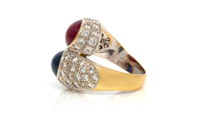 Ring finely crafted in 18K white gold with Cabochon Ruby and Sapphire surrounded with diamonds.  The Cabochon Sapphire weighing approximately 4.00 carat. The Cabochon Ruby weighing approximately 4.00 carat.  The diamonds weighing approximately 3.20