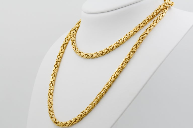 This Byzantine link 18k yellow gold necklace is 36' in length and 5mm wide. It has an integrated clasp with safety and has a polished finish.