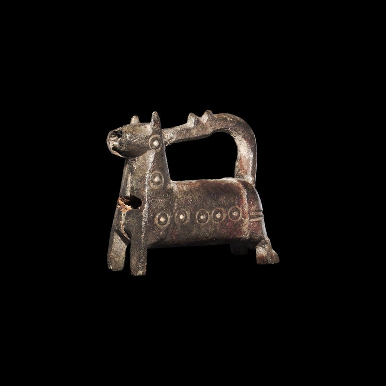 A bronze barrel-lock formed as a standing horse with curved legs, ring-and-dot motifs to the body, the recurved tail forming the hasp.   33.2 grams, 36mm (1 1/2