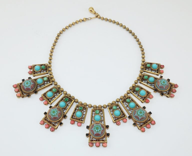 This early 20th Century bib necklace incorporates an ornate Byzantine style design with gold tone metal beads detailed with a lattice pattern suspending filigree drops embellished with glass in coral, turquoise blue and jade green.  The overall look