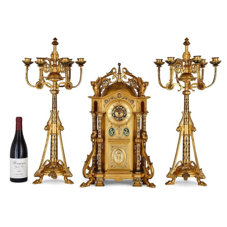 Byzantine style gilt bronze and champlevé enamel clock garniture by Raingo Frères French, late 19th century Measures: Clock: Height 55cm, width 34cm, depth 25cm Candelabra: Height 67cm, width 31cm, depth 28cm  The present clock set is by Raingo
