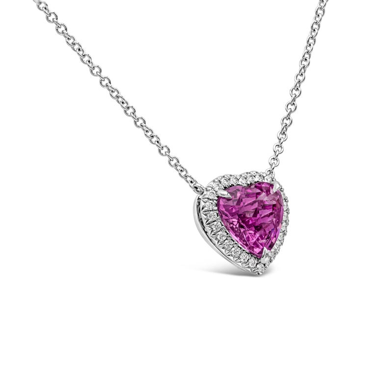 A rare piece of jewelry showcasing a 2.92 carat vivid pink sapphire in a heart shape, surrounded by a single row of round brilliant diamonds. Pendant is suspended on an 18 inch 18k white gold chain. Center sapphire is certified by C. Dunaigre.