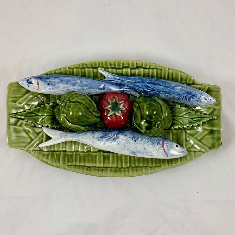 A Palissy style Trompe L'oeil Majolica glazed hanging wall plaque showing fish and vegetables on a green woven basket, circa early to the mid-20th century, Caldas da Rainha, Portugal.  The oblong plaque features a dimensional grouping of three