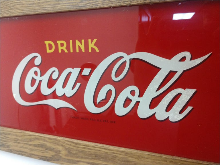 Fabulous 10 x 21 reverse painted glass coca cola sign from the twenties. In excellent vintage condition with a bit of fixing on the upper right corner. Made by the Price Bros. from Chicago for the Coca Cola bottling co.