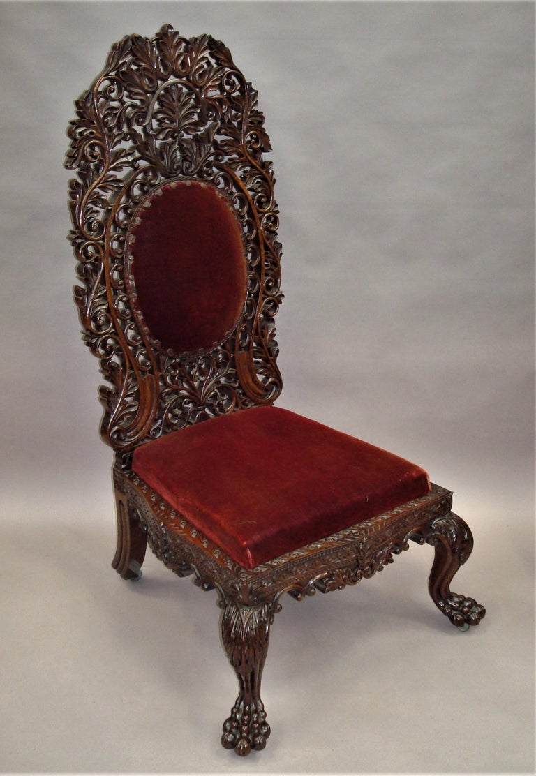 An impressive mid-19th century Anglo-Indian carved padouk side chair; the unusually high back profusely carved and pierced with scrollwork, foliage and acanthus leaves with a central oval upholstered padded panel. The seat frame intricately carved