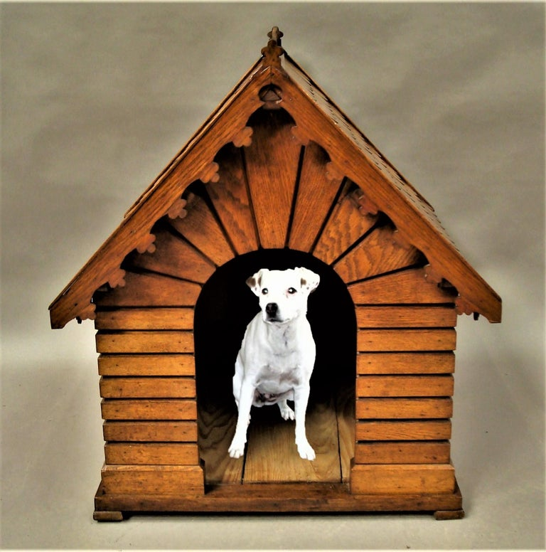 Unusual 19th century oak dog house or dog kennel; in the rare form of a house in well figured honey coloured oak; the pitched tiled roof with a fleur de lys shaped parapet and eaves with a similar design, above the simulated brickwork sides with