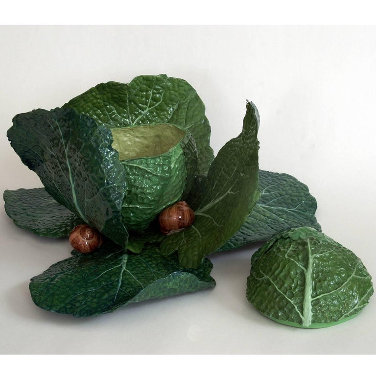 This extremely lifelike papier-maché sculpture depicts a bright green cabbage with its leaves opening up to reveal a small snail. The piece is hand-painted with natural pigments and then lacquered. The glossy finish is achieved by polished resin.