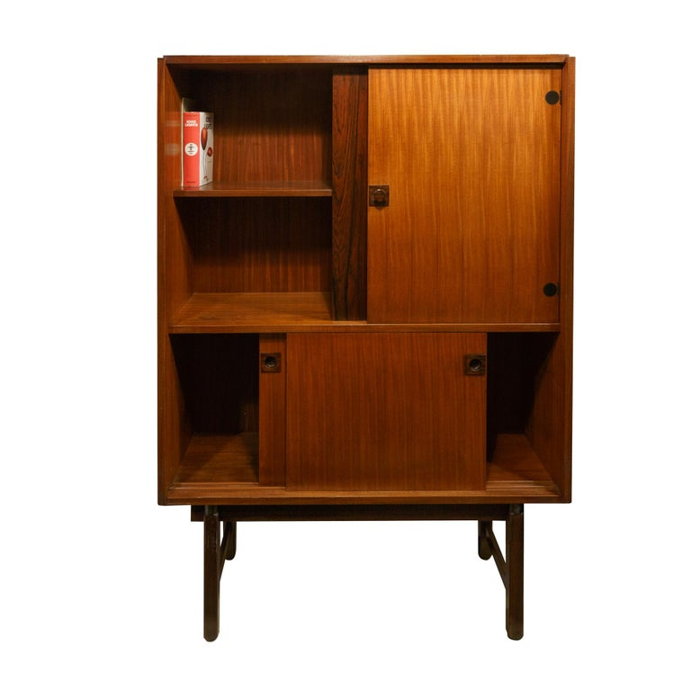 Cabinets by Gianfranco Frattini from Mobili Cantu, Italy, 1960s. The cabinet in the upper part has an open compartment and closed part with door. In the lower part two sliding doors. The main feature is the high legs and the round and black finishes