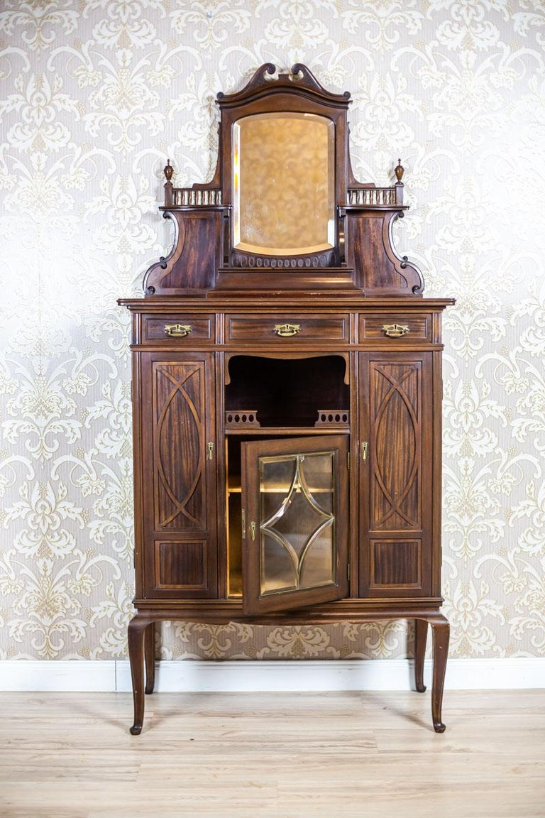 We present you a piece of furniture made of mahogany wood and veneer. All is from the turn of the 19th and 20th centuries. The cabinet is composed of a base on high legs and an add-on unit in the form of a wall with a mirror and a small