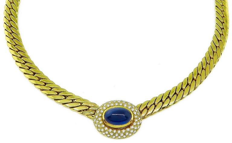 This elegant 18k yellow gold necklace centers a lovely cabochon cut sapphire that weighs approximately 9.00ct. The sapphire is accentuated by sparkling round cut diamonds that weigh approximately 1.40ct. graded G color with VS clarity. The necklace