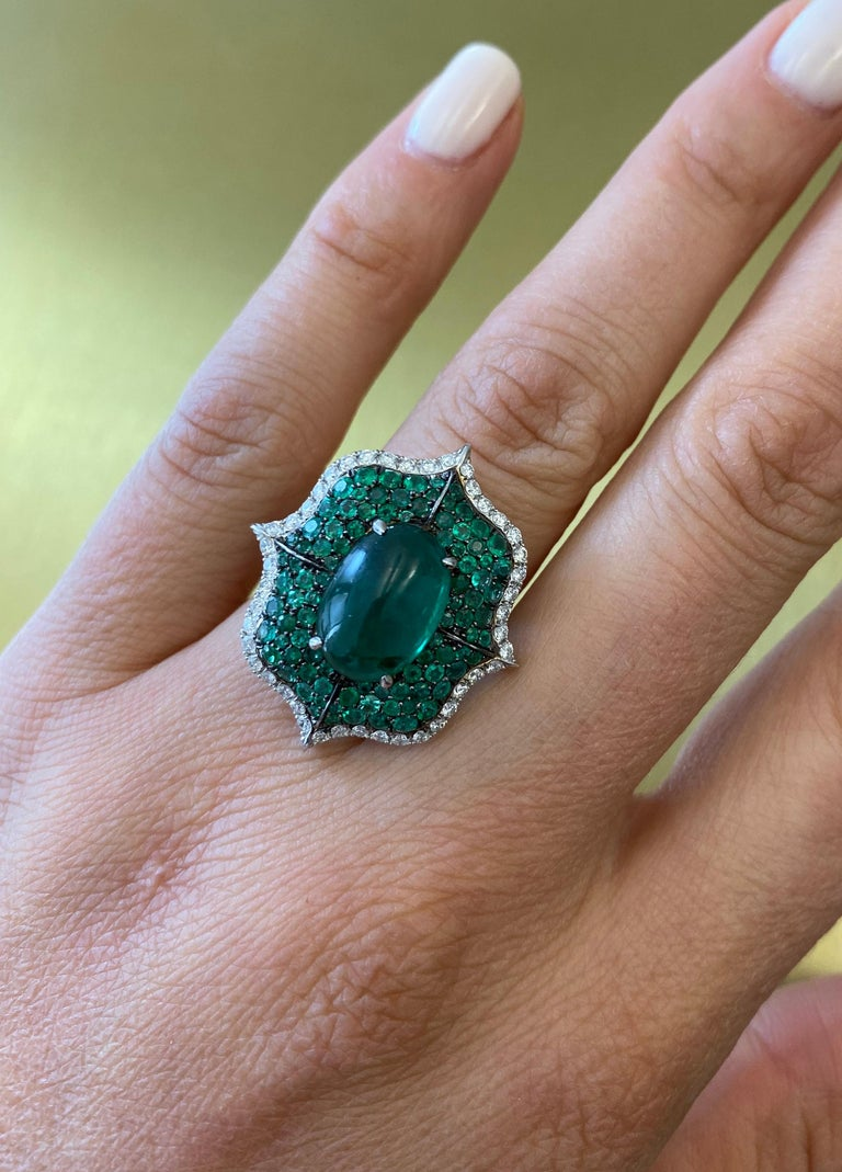 A Cabochon Emerald Ring accented by 102 pave diamonds and 92 pave green emeralds set in 18k white gold. Center Cabachon Emerald is 3.64ct. Total carat weight of Diamonds is 0.90cts and total carat weight of emeralds is 1.25cts. This piece is
