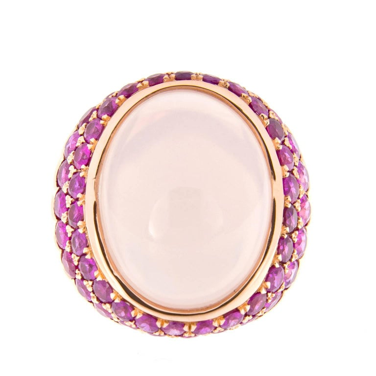 Pretty in pink! The beautiful oval cabochon rose quartz is 19mm x 16mm and is surrounded by two rows of stunning pink sapphires. Ring crafted in 18k rose gold. Ring Size 6. Weighs 17.8 grams. Handmade in New York  Pink Sapphires 4.0 cttw