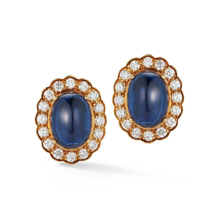 Cabochon Sapphire & Diamond Halo Earrings   2 cabochon sapphires approximately 18.00 cts.  32 round diamonds approximately 2.00 cts  18 karat yellow gold Measurements: .78