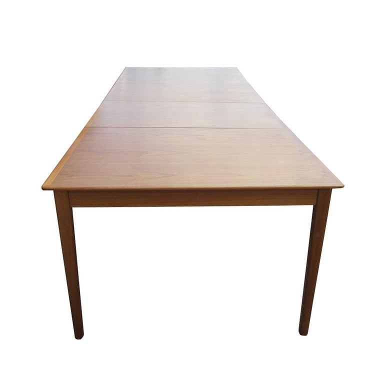 A sleek Danish dining table with two leaves by Cado. Extremely versatile, with an adjustable fifth leg for extra stability, this dining table can comfortably seat anywhere from four to ten guests, for either an intimate dinner or a dinner party.