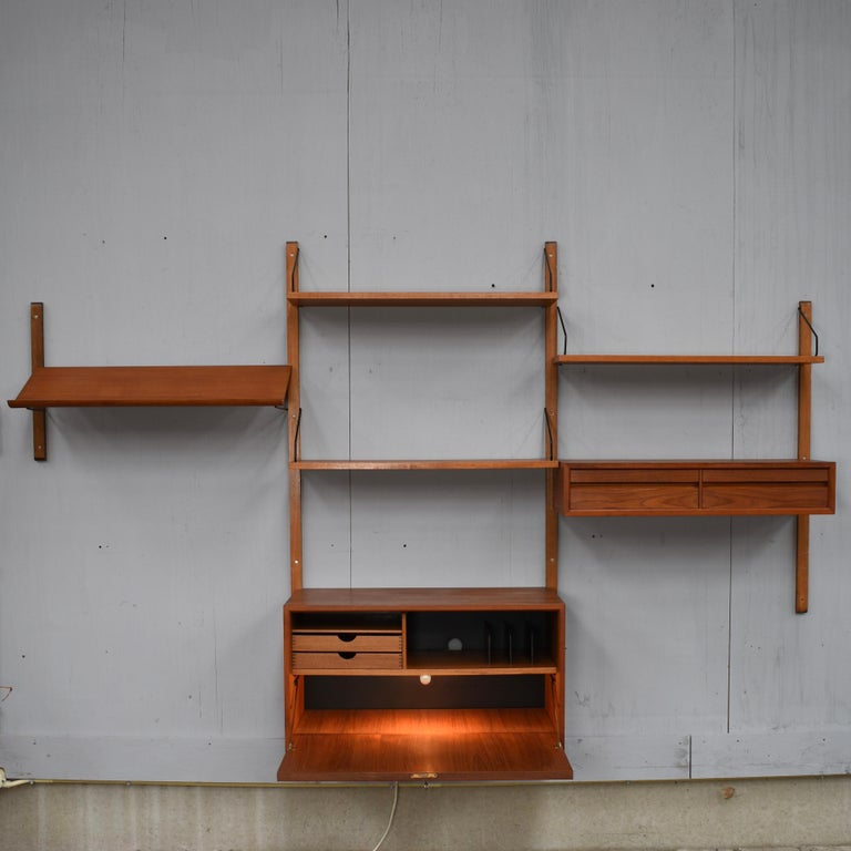 Beautiful Royal series wall unit by Poul Cadovius with much wanted angled lecture shelve. In a beautiful warm wood color and in good condition. This unit features:  – 1 much wanted lecture shelve  – 1 desk cabinet with built-in light  – 1