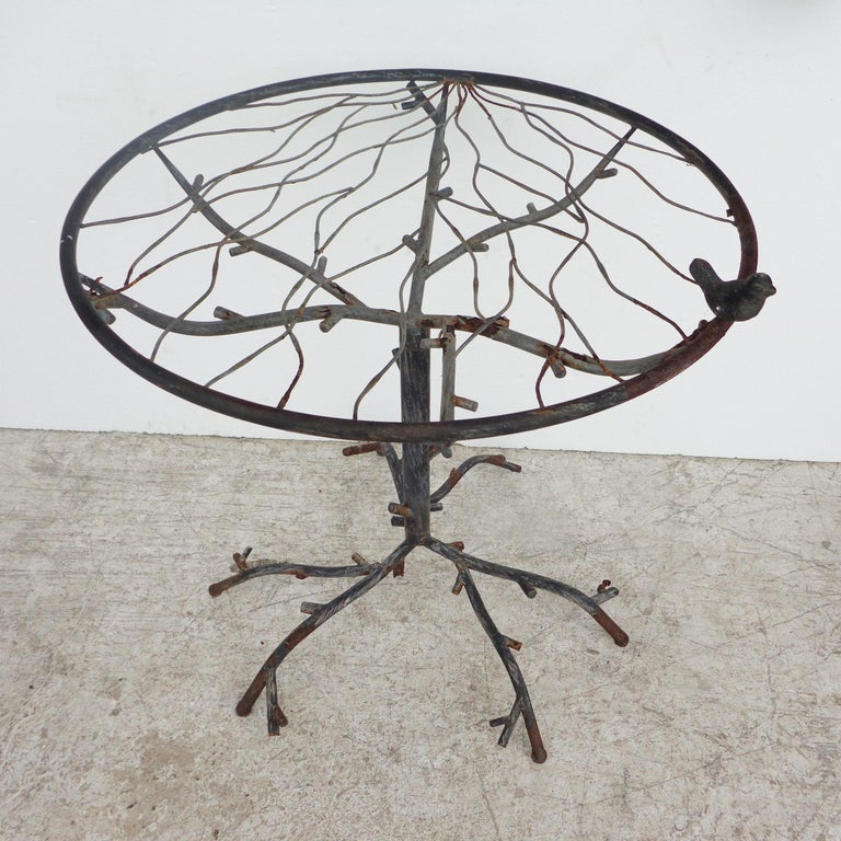 Cafe table in the manner of Alberto Giacometti  Beautiful hand forged iron table with glass top  Features carved tree branches under glass and at base with a small bird on the top.