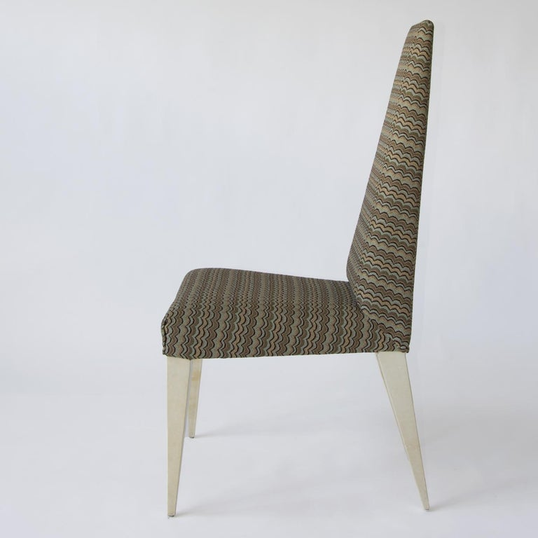 With sleek lines and a unique design, the Kajal dining chair features sturdy, tapered legs covered with natural light-toned parchment for a sophisticated and elegant look. Upholstered in a multi-color fabric that features a subtle pattern in neutral