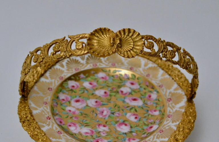 Cake stand ormolu-mounted painted porcelain plate with a gilt bronze handle. First half of the 19th century. The porcelain finely painted with roses and gilt.