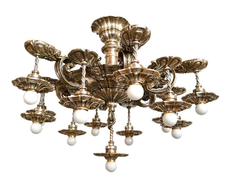 This absolutely stunning E.F. Caldwell chandelier is made of lovely silver plated brass and features intricate detailing throughout. Above the body of the fixture is a simple canopy assembly, with a floral detailed slip ring that holds the elegant