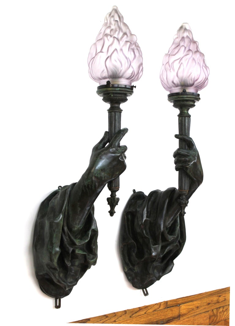 American Gilded Age or Belle Époque pair of heavy patinated cast bronze hand torchiere wall sconces, attributed to Edward F. Caldwell & Co. in New York City. The pair of sconces has elaborate drapery from which life-sized hands emerge, holding up