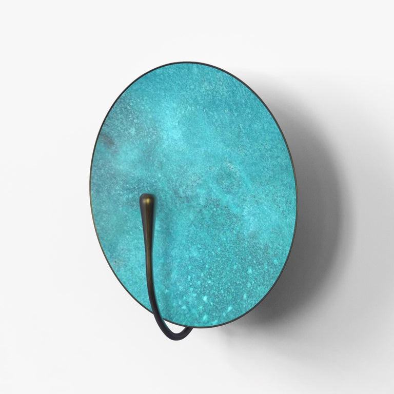 A gentle silhouette of the circular plate makes up this unique wall light. Inspired by planet-like appearances and textures, a Vedigris patina is applied to create this unique finish. Please note the process is slightly random and each plate has a