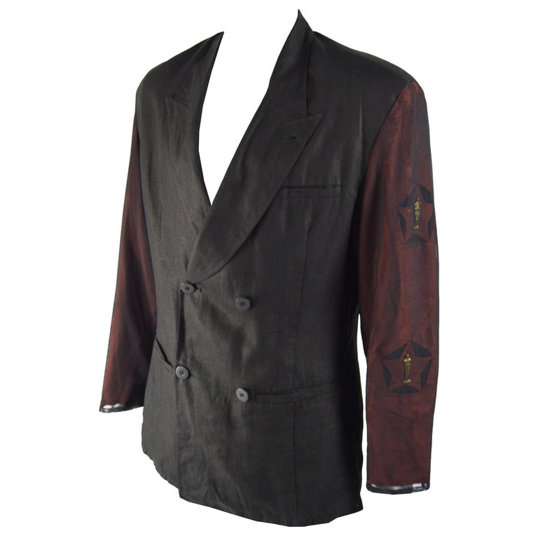 An amazing and ultra rare vintage mens blazer jacket from the 80s by genius Italian fashion designer duo, Calugi e Giannelli. In a black linen with red cut out sleeves that are embellished with Oscar statues and then covered in mesh for a