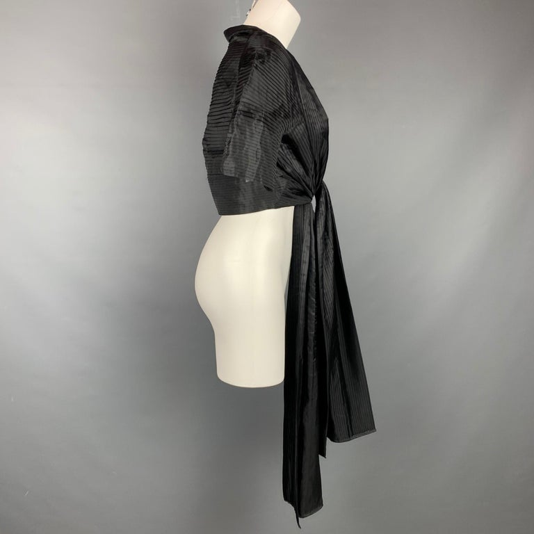 CALVIN KLEIN capelet comes in a black pleated material featuring long panel details and a open front.  Pre-Owned Condition. Marked: Size tag removed.  Measurements:  Shoulder: 15 in. Bust: 34 in. Sleeve: 14 in. Length: 14.5 in.
