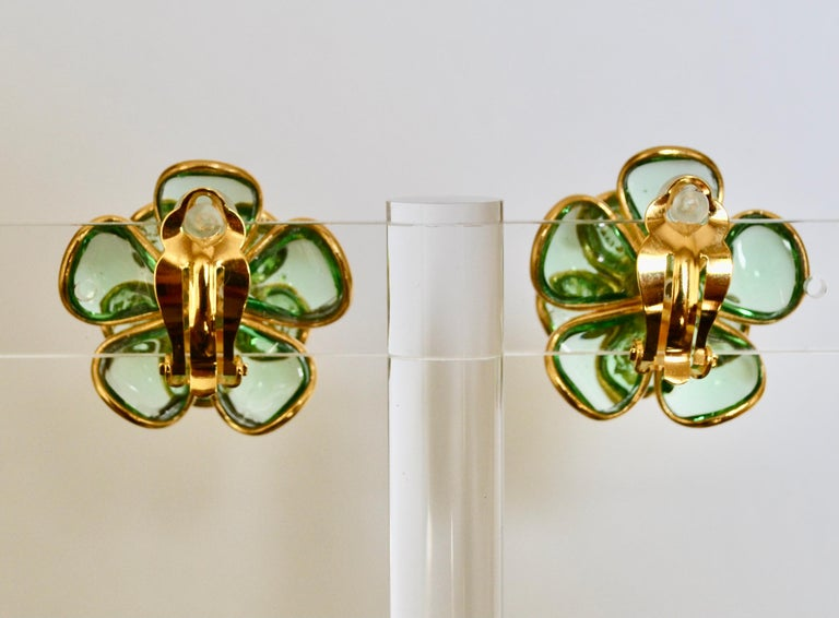 Camelia flower clip earrings made in Pate de verre, an intricate process used by the atelier de Gripoix for the House of Chanel. These earrings were made by former artisans of the atelier of Gripoix. Green pate de verre with gold leaves inserted.